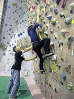 小林さんに手伝ってもらいながら、初めて壁を登る中村キャスター(国分寺市のクライミングジムで)