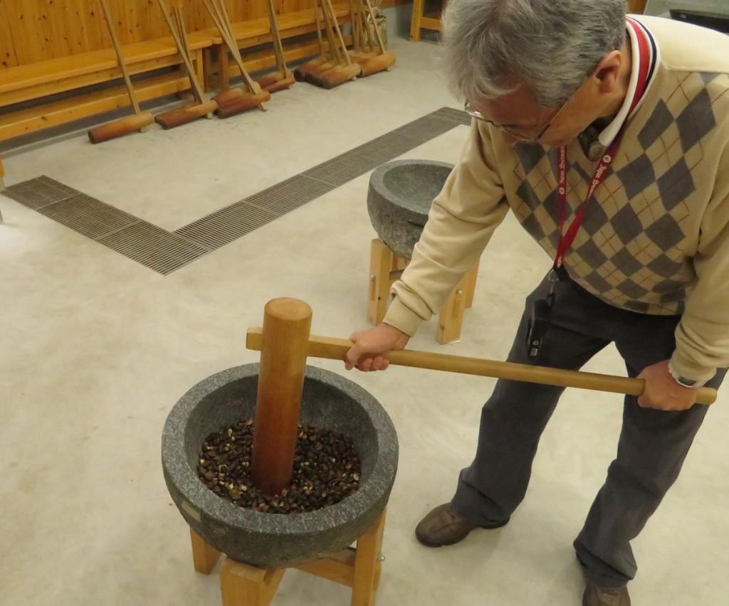 椿の実を石臼でつぶし、蒸したあと、圧搾機を使いながらも自分の力で搾りだす椿油作り