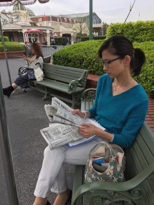 小倉アナもその一人。慣れないディズニーランドに不安げ。新聞を読み出す次第